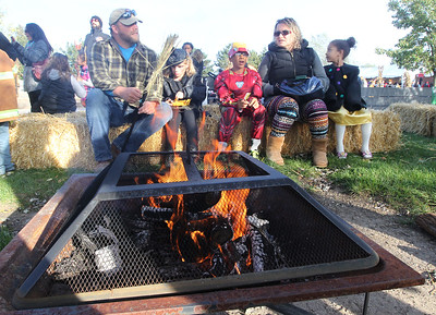 Candace H. Johnson-For Shaw Media Visitors stay warm by the fire during the Haunted Trail & More Family Fall Festival at the Lindenhurst Park District's Lippert Community Center in Lindenhurst. (10/13/18)