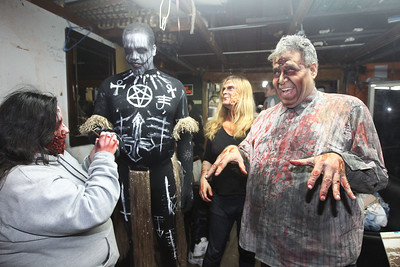 Candace H. Johnson-For Shaw Media Carla Carrillo, 18, of Round Lake works on painting Jason McDay's, of Algonquin voodoo monster costume as he stands next to Nicole Smith, of Gurnee and Jim Alvardo, of Waukegan before they greet visitors at the Realm of Terror Haunted House on Rollins Road in Round Lake Beach. (10/13/18)