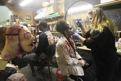 Candace H. Johnson-For Shaw Media Jason McDay, of Algonquin and Tatiana Freeman, 17, of Round Lake get their ghoul makeup done by  Stevie Calabrese, 29, of Round Lake and Rena Beyers, 18, of Wauconda, both makeup artists, at the Realm of Terror Haunted House on Rollins Road in Round Lake Beach. (10/13/18)