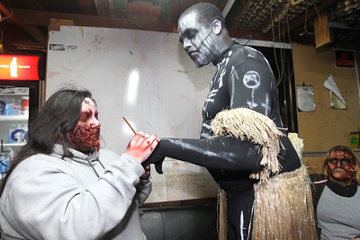 Candace H. Johnson-For Shaw Media Carla Carrillo, 18, of Round Lake paints different pictures on Jason McDay's, of Algonquin, voodoo monster costume at the Realm of Terror Haunted House on Rollins Road in Round Lake Beach. Julie Koenig, of Round Lake Heights sat close by.(10/13/18)