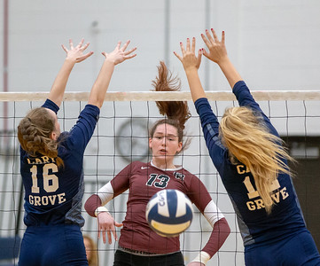 Prairie Ridge's Samantha Lockwood (middle) spikes the ball between Cary-Grove defenders Julia Rice (Right) and Sydney Csoka (left) Thursday, October 18, 2018 in Carry. Prairie ridge wins the match in two straight sets and clinches the Fox Valley Conference title.  KKoontz – For Shaw Media
