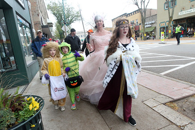 Candace H. Johnson-For Shaw Media Izzy Mattauch, 6, Hannah Stuart, 7, her mother, Marci, and sister, Kaylee, 11, all from Antioch walk together on Main Street to get candy from businesses during Treat the Streets in downtown Antioch. (10/20/18)