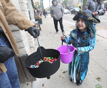 Candace H. Johnson-For Shaw Media Abby Sandoval-Rodriguez, 5, of Waukegan looks up to get some candy from Jeff Kingsley with Timeless Treasures during Treat the Streets in downtown Antioch. (10/20/18)
