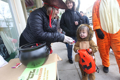 Candace H. Johnson-For Shaw Media Becca Pfeiler, of Crystal Lake, with Something Sweet hands out some candy to Layla Krivickas, 2, of Lake Villa on Main Street during Treat the Streets in downtown Antioch. (10/20/18)