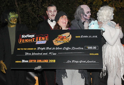 "Candace H. Johnson-For Shaw Media Contestant Allison Jornlin, of Milwaukee, Wis., a paranormal investigator, holds up her check after laying in a coffin during the 30 Hour Coffin Challenge for Fright Fest at Six Flags Great America in Gurnee. Performers from the show, ""Love at First Fright,"" stood behind her. Six winners including, Allison, received $300, two 2019 Gold season passes to Great America, two Express Haunted House wrist bands, their coffin and a chance to be in the Uprising Parade. (10/21/18)"