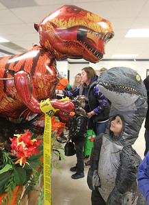 Candace H. Johnson-For Shaw Media Eric Kogut, 5, of Round Lake, dressed as a raptor, looks up at an inflatable dinosaur on display during the Great Pumpkin Celebration at the Robert W. Rolek Community Center in Round Lake.(10/20/18)