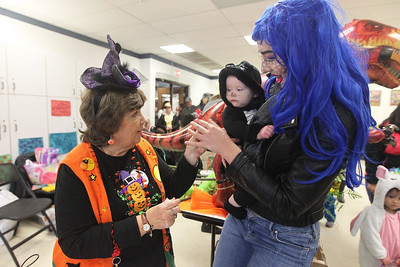 Candace H. Johnson-For Shaw Media Debbie Allen, of Ingleside, head of youth services for the Round Lake Area Public Library, talks with Rosie Diefenthaler, ten-months-old, of McHenry, as she hands a lollipop to her Aunt Amanda, from Chicago, for her during the Great Pumpkin Celebration at the Robert W. Rolek Community Center in Round Lake.(10/20/18)