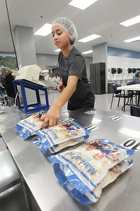 Candace H. Johnson-For Shaw Media Ashley Perez, of Waukegan lays out full MannaPacks waiting to be put into a box during a packing session at Feed My Starving Children in Libertyville. (10/29/18)