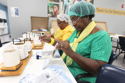 Candace H. Johnson-For Shaw Media Dr. Alfreda Rhodes-King and Rosie Elder, both of Waukegan and registered nurses with a professional nursing organization, put expiration date stickers on MannaPacks during a packing session at Feed My Starving Children in Libertyville. (10/29/18)