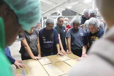Candace H. Johnson-For Shaw Media Volunteers including students from the Warren Township High School Student Council O'Plaine campus stand around the boxes of food they packaged to pray before they are shipped out during a packing session at Feed My Starving Children in Libertyville. (10/29/18)