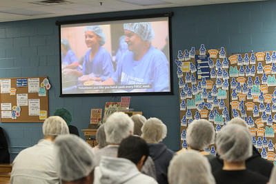 Candace H. Johnson-For Shaw Media Volunteers wear hair nets and watch a video before heading into the packing room to fill up MannaPacks with nutritional meals during a packing session at Feed My Starving Children in Libertyville. (10/29/18)