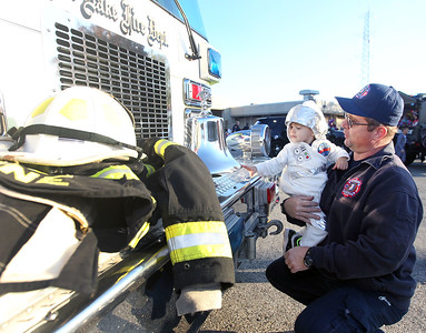 Candace H. Johnson-For Shaw Media Rich Hoehne, chief engineer with the Fox Lake Fire Protection District, (on right) shows Anton Kaye, 1, of Lake Villa a bell on a squad during Halloween Howl at the Fox Lake Police Department on Route 59 in Fox Lake. Anton was at the event with his mother, Stephanie Kaye.(10/29/18)