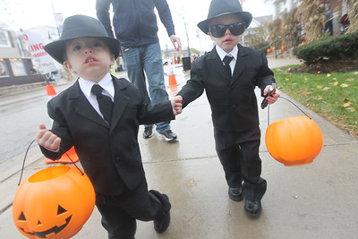 Candace H. Johnson-For Shaw Media Calvin Eskoz, 2, of Wauconda and his twin brother, Fitz, walk together during Trick or Treat Main Street in Wauconda.The boys were with their parents, Steve and Laycie, and baby sister, Elsie, five-weeks-old. (10/28/18)