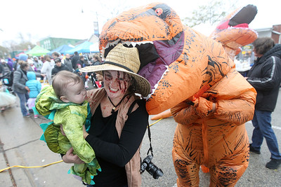 Candace H. Johnson-For Shaw Media Linda Rickerson, of Cary holds her daughter, Madeline, six-months-old, as her husband, Ryan, has some fun with them as a dinosaur during Trick or Treat Main Street in Wauconda. (10/28/18)