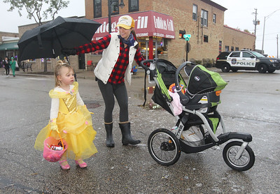 Candace H. Johnson-For Shaw Media Sarah Graybill, of Wauconda holds an umbrella over her daughter, Esme, 3, dressed as Belle, to keep her dry and pushes her other daughter, Madeleine, seven-months-old, during Trick or Treat Main Street in Wauconda. (10/28/18)