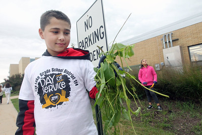 Candace H. Johnson-For Shaw Media Stanton's Logan Hamm, 11, of Fox Lake shows off the weeds he pulled at Grant Community High School during Fox Lake Grade School District 114's 5th Annual Day of Service. Angelina Rico, 11, of Fox Lake stood close by. (9/27/19)