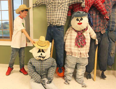 Candace H. Johnson-For Shaw Media Stanton's Johnny Pause, 11, of Spring Grove puts a cowboy hat on a scarecrow just made by middle school students for the upcoming Grant Township & Village of Fox Lake Fall Festival at the Grant Township community room during Fox Lake Grade School District 114's 5th Annual Day of Service. (9/27/19)