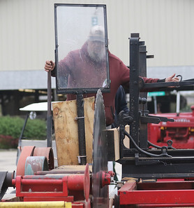 Candace H. Johnson-For Shaw Media John Bauer, of Lake Zurich demonstrates how he cuts logs into boards with a saw mill from the late 1800's during the Lake County Farm Heritage Association's Farm Heritage & Harvest Festival at the Lake County Fairgrounds in Grayslake.  (9/29/19)