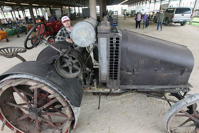Candace H. Johnson-For Shaw Media Scott Kaminski, of Grayslake shows off his son, Scott's, 1921 International Harvester tractor, model 816, during the Lake County Farm Heritage Association's Farm Heritage & Harvest Festival at the Lake County Fairgrounds in Grayslake. The tractor runs on kerosene, it is all original and has never been restored. It also was made in Chicago and shipped to Lake County, sold in Libertyville and has since stayed in Lake County. (9/29/19)