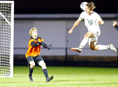 Crystal Lake South Alex Canfield (13) heads a ball past Crystal Lake Central goalkeeper Joseph Moore (1) on Tuesday, October 8, 2019, at Crystal Lake Central High School in Crystal Lake, Ill. The Crystal Lake South Gators defeated the Crystal Lake Central Tigers 3-1.