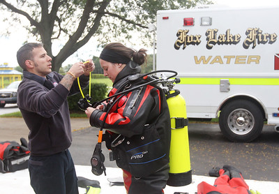Candace H. Johnson-For Shaw Media Sam Santiago helps Corinne Bauer, both firefighter paramedics with the Fox Lake Fire Protection District, with her scuba gear before she gives a demonstration on water rescues during the Grant Township & Village of Fox Lake Fall Festival at Grant Township Center in Ingleside.  (10/6/19)