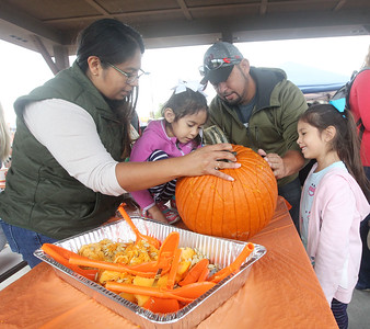Candace H. Johnson-For Shaw Media Karla and Jose Castro, of Round Lake work with their daughters, Angie, 4, and Gianna, 6, on carving a pumpkin during the Grant Township & Village of Fox Lake Fall Festival at Grant Township Center in Ingleside.  (10/6/19)