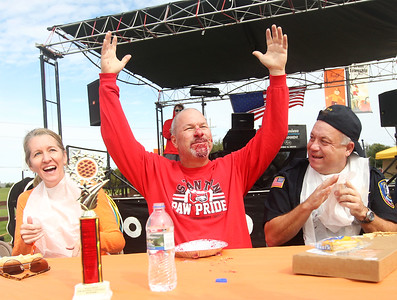 Candace H. Johnson-For Shaw Media Jeff Sefcik, (center) principal of Stanton Middle School, celebrates winning the pie eating contest as he sits next to his wife, Christine, superintendent of Grant Community High School, and Jimmy Lee, police chief of the Fox Lake Police Department, during the Grant Township & Village of Fox Lake Fall Festival at Grant Township Center in Ingleside.  (10/6/19)