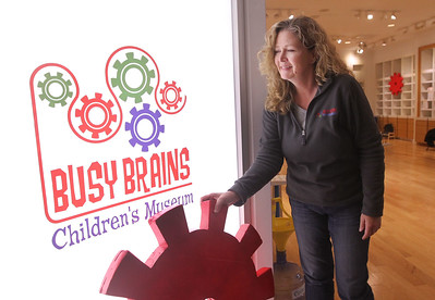 Candace H. Johnson-For Shaw Media Heidi Alexander, of Crystal Lake, director of operations, adjusts the holding gear decoration outside of the Busy Brains Children's Museum Pop Up Museum at Hawthorn Mall in Vernon Hills. The decoration was donated by the Grayslake North Marching Band, which had used the gear for a performance. (10/12/19)
