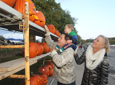 Candace H. Johnson-For Shaw Media Gary Hannigan, of Spring Grove, his son, Hunter, 2, and Pam Roberson, of Katy, Texas put their carved pumpkins on a long wall along Community Garden Green for everyone to see during the Fox Lake Pumpkin Jubilee. (10/12/19)