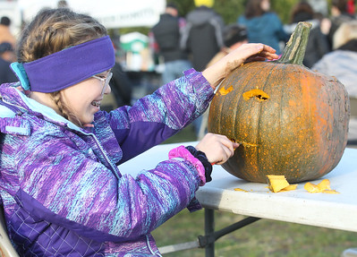 Candace H. Johnson-For Shaw Media Fiona Carlson, 11, of Round Lake carves a pumpkin during the Fox Lake Pumpkin Jubilee at Community Garden Green in Fox Lake. (10/12/19)