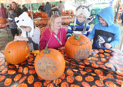 Candace H. Johnson-For Shaw Media Mary Tascher, of Fox Lake helps her grandchildren, Layla Knoblock, 6, of Round Lake, her brother, Henry, 8, and Mason Terrell, 8, of Ingleside carve pumpkins during the Fox Lake Pumpkin Jubilee at Community Garden Green in Fox Lake. (10/12/19)