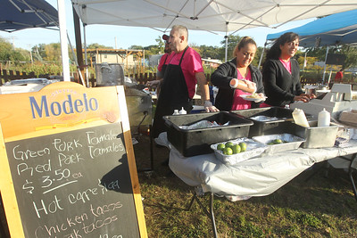 Candace H. Johnson-For Shaw Media Roy Auza, Victor Morales, Perla Luna and Mirza Hernandez, all with La Cocina Mexican Restaurant in Fox Lake, serve tamales and tacos during the Fox Lake Pumpkin Jubilee at Community Garden Green in Fox Lake. (10/12/19)