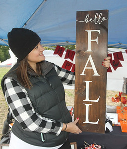Candace H. Johnson-For Shaw Media Sara Snelten, of Lake Villa with Buffalo Plaid Studios, shows off one of the handmade signs she had for sale in the Artisan Market during the Fox Lake Pumpkin Jubilee at Community Garden Green in Fox Lake. (10/12/19)