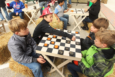 Candace H. Johnson-For Shaw Media Porter Crammond, 11, of Lake Villa and Derrion Litchfield, 10, of Antioch play a game of outdoor checkers with their brothers, Dominic Litchfield and Cael Crammond, both 9, during the Village of Lake Villa's Celebration of Fall on Cedar Avenue in Lake Villa. (10/12/19)