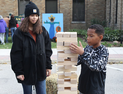 Candace H. Johnson-For Shaw Media Deja Robinson, 15, of Round Lake and her brother, Devin, 10, play Jenga on Cedar Avenue during the Village of Lake Villa's Celebration of Fall. (10/12/19)