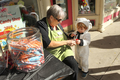 Candace H. Johnson-For Shaw Media Pat Benes with the Something Sweet Candy Shoppe gives some candy to Jimmy Plath, 2, of Antioch during Harvest Fest for Treat the Streets in downtown Antioch. (10/19/19)