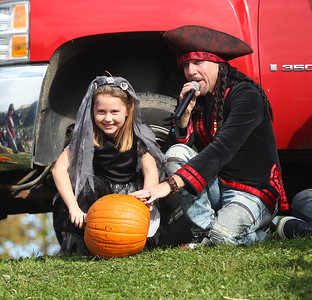 Candace H. Johnson-For Shaw Media Fiona Orutar, 7, of Lake Villa sits next to DJ Goldy, of Spring Grove as she gets ready to push her pumpkin down the hill as she competes in the Pumpkin Roll during Harvest Fest at the William E. Brook Entertainment Center in Antioch. (10/19/19)