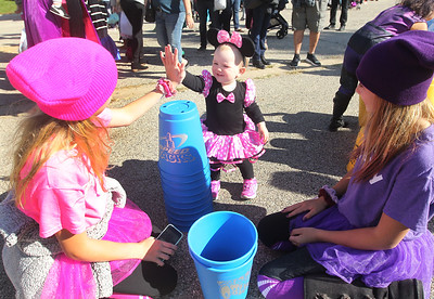 Candace H. Johnson-For Shaw Media Volunteers Kayliana Losinger, 13, and Sadie Myers, 12, both of Antioch get high fives from Sydney Brodell, eighteen-months-old, of Grayslake as they help her play with Speed Stacks during Harvest Fest at the William E. Brook Entertainment Center in Antioch. (10/19/19)