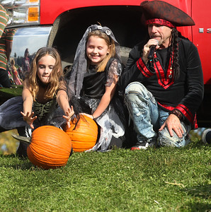 Candace H. Johnson-For Shaw Media Sienna Gettelman, 10, of West Bend, Wis., sits next to Fiona Orutar, 7, of Lake Villa and DJ Goldy, of Spring Grove as she pushes her pumpkin down the hill as she competes in the Pumpkin Roll during Harvest Fest at the William E. Brook Entertainment Center in Antioch. (10/19/19)