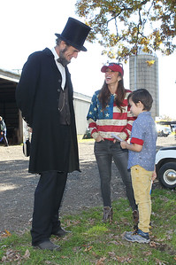Candace H. Johnson-For Shaw Media President Abraham Lincoln portrayed by Kevin Wood, of Oak Park talks with Lauren Atchinson, of Grayslake and her son, Sawyer, 7, as he holds a President Lincoln flashcard during Hainesville's annual Civil War Encampment & Battle at the Northbrook Sports Club in Hainesville. (10/20/19)