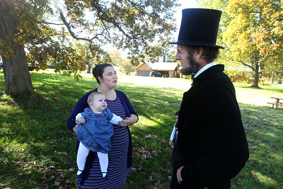 Candace H. Johnson-For Shaw Media Danielle Gosnell, of Round Lake Beach holds her daughter, Tziporah, seven-months-old, as she speaks with President Abraham Lincoln portrayed by Kevin Wood, of Oak Park during Hainesville's annual Civil War Encampment & Battle at the Northbrook Sports Club in Hainesville. (10/20/19)