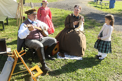 "Candace H. Johnson-For Shaw Media Alice Urven, 7, of Fond du Lac, Wis., and Layla Schliz, 5, of Milwaukee, Wis., listen to John and Elaine Masciale, of Palatine play a song called, ""Old Dan Tucker,"" during Hainesville's annual Civil War Encampment & Battle at the Northbrook Sports Club in Hainesville. (10/20/19)"