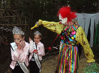 Candace H. Johnson-For Shaw Media Charlotte Romig, 11, and Nicoletta Katris, 8, both Lindenhurst queens walk past a clown portrayed by Dylan Snow, 19, of Antioch in the Haunted Trail during the Haunted Trail and Bonfire at Forest View Park in Lindenhurst. The event was hosted by the Lindenhurst Park District. (10/19/19)