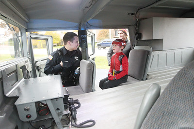Candace H. Johnson-For Shaw Media Patrol Officer Michael Lira talks with Bradley Szarban, 6, of Fox Lake and his mother, Erin, about the police Hummer he is sitting in, which is used for floods, during Halloween Howl at the Fox Lake Police Department. (10/28/19)