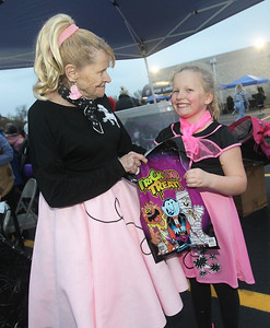 Candace H. Johnson-For Shaw Media Cindy Irwin, of Fox Lake gives a bag of candy to Kaylen Eveland, 7, of Richmond, both dressed in 50's costumes, during Halloween Howl at the Fox Lake Police Department. (10/28/19)