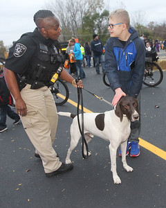 Candace H. Johnson-For Shaw Media C.C. Miller, a K-9 handler with the Metra Police, talks with Tyler Leanes, 15, of Fox Lake about Lord, a German Shorthaired Pointer and a bomb dog, during Halloween Howl at the Fox Lake Police Department. (10/28/19)