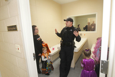 Candace H. Johnson-For Shaw Media Krystle Warnock, of Ingleside and her children Juliette, 2, Joselyn, 4, and Juliana, 7, stop in the Interrogation room as they talk with Police Officer Andrew Harlin while taking a jail cell tour during Halloween Howl at the Fox Lake Police Department. (10/28/19)