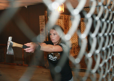 Candace H. Johnson-for Shaw Media Molly Trefry, of Ingleside, manager, stands in a fenced in pit area holding a hatchet as she aims for her target during the grand opening of the Lumberjaxe Axe Lounge on Peterson Road in Libertyville. A second location for the Lumberjaxe Axe Lounge will open in Gurnee Mills at the end of November.  (10/1/21)