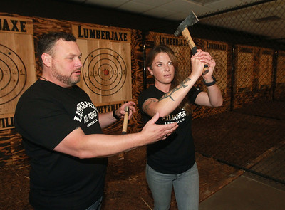 Candace H. Johnson-for Shaw Media Jason Wright, of Libertyville, owner, works with Molly Trefry, of Ingleside, manager, on how to throw a hatchet at a target during the grand opening of the Lumberjaxe Axe Lounge on Peterson Road in Libertyville. A second location for a  Lumberjaxe Axe Lounge will open in Gurnee Mills at the end of November.  (10/1/21)