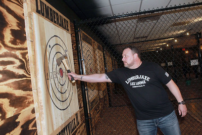 Candace H. Johnson-for Shaw Media Jason Wright, of Libertyville, owner, pulls his hatchet out of the target after throwing it during the grand opening of the Lumberjaxe Axe Lounge on Peterson Road in Libertyville. A second location for the Lumberjaxe Axe Lounge will open in Gurnee Mills at the end of November.   (10/1/21)